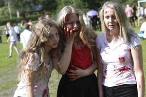 Delar ur skräckfilmslagets medlemmar. En ung kvinna, som nyss har blivit jagad av en mördare, flankerad av två zombies.