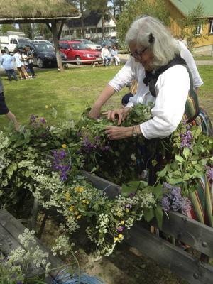Evy Hörnqvist kan konsten att sätta blommor i Midsommarstången.   Foto:  Monica Nyström