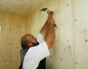 Harald Lange från Tyskland följde med från fabriken för att montera ihop ekohuset. Han berättar att de satt upp ett tiotal hus, men det här är det första i Sverige. Här sätter han in en av träpluggarna i väggen.