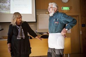 Stig Persson demonstrerar den underbyxa som boende på Backsippan erbjuds för att lindra stötar mot höften vid fall. Lea Lindkvist från Backsippan ser på.