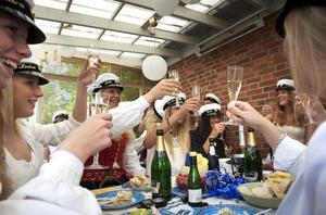 Klara Sahlén och Lovisa Åkesson skålar med sina klasskompisar på champagnefrukosten.