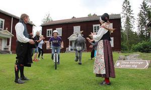 Kultur och idrott möts under aktivitetshelgen. Oskar Wiklander och Hälge springer förbi publiken. Vid målgången står Lennart Östningsgårds och Mona Rosenqvist.