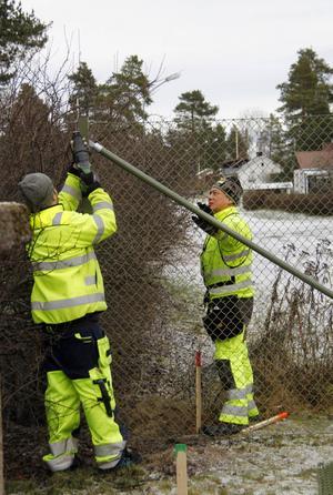 Montörerna Andreas Jansson och Chidchep Jaiyawat kompletterar med ytterligare en bit staket vid brandstationen.
