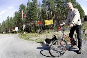 """FARLIGT. """"Jag brukar plocka bär här, men aldrig när det skjuts. Det finns tydlig information om när de ska öva, dessutom syns flaggorna på långt håll"""" säger Marmabon Tommy Wallin, här på cykeltur med hunden Pluto."""
