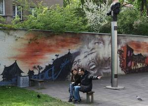 Kulturhuvudstad 2009. Två Vilniusbor vilar benen framför en väggmålning.Foto: Mindaugas Kulbis/AP/Scanpix