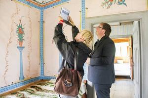 Ingalill Nyström leder det tvärvetenskapliga projektet. Hon och Lars Nylander tittar närmare på målningarna.