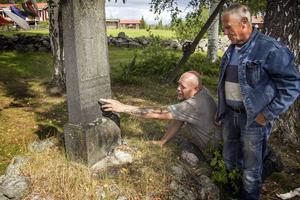 Delsbo Forngårds vaktmästare Tord Andersson och Stålbergs släkting Rune Eriksson. Det är inte lätt att se stenens text. Men om man tar fingertopparna till hjälp känner man bokstäverna:
