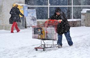 Kamp med kundvagn i blötsnön vid Arlandastad norr om Stockholm i snöovädret på lördagen. I Ångermanland utfärdar SMHI klass 1-varning.