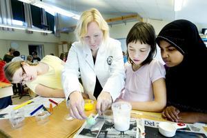 """Koncentrerade. Läraren Veronica Östman visar femteklassarna Tilde Olsson, Julia Eriksson och Naung Mai Naung Mai hur de ska blanda Latex, Hydrocarb, Bermocoll och vatten till en brytbas som ska användas för att blanda fram färg. """"Kul att få testa"""", säger tjejerna om experimentet."""