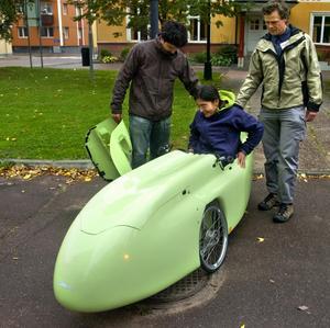 Beatrix Strid får hjälp ned i den racingliknande sittbrunnen av cykelbilens utvecklare Frederik Van De Walle och projektets pådrivare Martin Strid. Ekipaget utan förare väger cirka 36 kilo. Foto:Johan Larsson