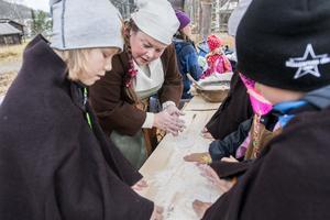 Pedagogen Lena Bengtsson hjälper William Lundin att baka vikingabröd medan hon berättar om vikingtidens matkultur.