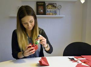 Linnéa tycker om att pyssla och gör mycket av julpyntet själv. Här gör hon en diamantformad juldekoration av rött papper.