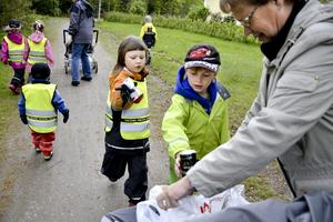 """Träffas varje vecka. I veckan träffades Laxå kommuns dagbarnvårdare och dagbarnen för att plocka skräp. Sofie Viklund och Emil Larsson slänger sina """"fynd"""" i Lisbeth Arvidssons påse."""