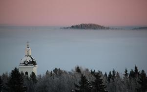 Fåker kyrkas kyrktorn skjuter upp ur dimman över Locknesjön