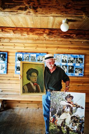 Spelmansbröderna Wernberg står i centrum på söndag när 50-100 spelmän kommer att hedra riksspelmännen från Medelpad. Göran Sjölén leder minneskonserten från scenen. Här står han med ett självporträtt av Evert som målades 1947 och en jättebild av Werner från början av 1970-talet.
