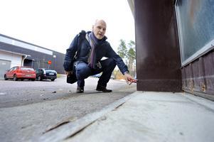 Fastighetsingenjör Lars Källgren på kommunfastigheter visar hur högt vattnet stod på yrkesdelens industriportar vid skyfallet den 21 augusti. Vattenranden har sökt sig kvar som en påminnelse om vad naturens krafter kan ställa till med.