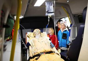 Så här ser det alltså ut inne i ambulansen när en patient ligger där. Maya, Anton och pappa Magnus Persson från Dvärsätt tittar intresserat på all teknik.