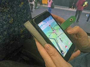 En person spelar succéspelet Pokémon Go på pendeltåget.