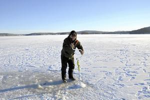 Nisse Tunströmmer ser till att borra sig ett nytt pimpelhål när fisken inte nappat.