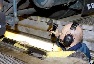 Kollar Axels axlar. Medan Thomas Holmquist från lastbilshytten kör bromsprov jobbar Mattias Österberg i gropen med att titta och känna på funktionerna axel för axel.