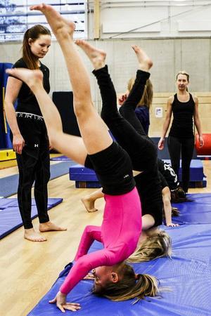 Hjälpledarna Sophie (närmast) och Annelie finns tillhands när gymnasterna tränar på huvudstående.