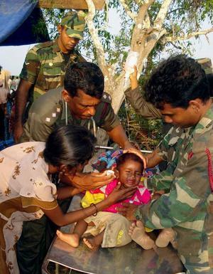 Ett tamilskt barn tas om hand av soldater från Sri Lankas armé. Det blodiga inbördeskriget mellan regeringen och de tamilska rebellerna har nått sitt slut. Nu krävs omfattande humanitära insatser till stöd för den tamilska civilbefolkningen. Foto: Scanpix