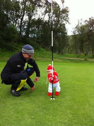 Det här är mitt barnbarn Tilda, 3,5 månad, som är ute på golfbanan tillsammans med pappa Johan för att få de första instruktionerna.