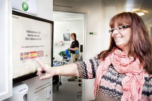 En pekskärm ersätter receptionen på Gävle Strands hälsocentral. Vårdenhetschefen Kicki Ceder visar hur den fungerar.
