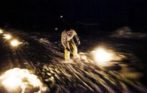 När det svenska möter det syriska. När skidåkning blir till något mänskligt, något som för folk samman. En man i 50-årsåldern som med stor obalans glider fram mellan raderna av tända marschaller.