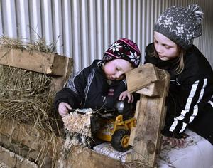 Barnen har en egen lekhörna i ladugården. Här är det Elias och Linnea som tar en paus från att hjälpa mamma och pappa.