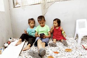 Omar, 3, Ahmed, 9, och Aisha, 1, har fått låna Maria Westins mobiltelefon. De spelar det populära barnspelet Subway surf.