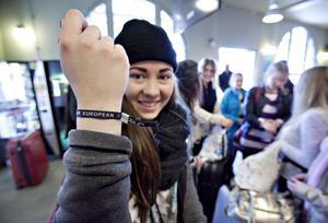 Frida Jonsson visar upp armbandet som eleverna ska bära under de tio dagarna som besöket i Spanien varar.