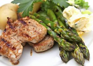 Tidig vårgrill med fläskfilé och grön sparris, antingen över glöd ute eller i grillpanna inne på spisen, bjuds med kokt primörpotatis och rört smör. Lättlagat och smakfullt.   Foto: Dan Strandqvist