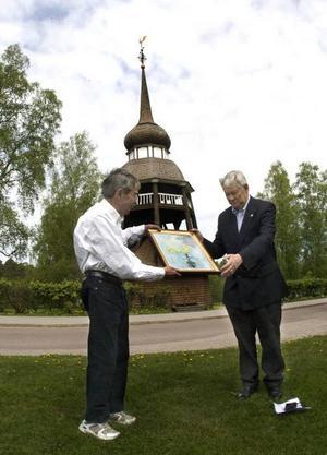 CEREMONI. Bo Engelberg, ordförande i Svenska kyrk- tuppsfrämjandet räckte över oljemålningen till Tomas Bornestaf, ordförande i stiftelsen Sällskapet Hälsinge regemente. Kyrktuppen, han höll uppsikt över dem från sin klockstapel.