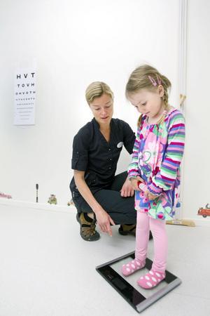 Siffrorna visar prick 16 när Hanna Larsson ställt sig på vågen. Barnläkaren Elisabeth Lindman kontrollerar.