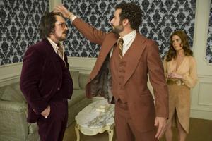 Christian Bales Irving har en utmanande frisyrlösning, Bradley Coopers FBI-agent fixar sitt hår med minipapiljotter och Amy Adams Sydney bär enormt djärva urringningar. Det finns en handling i