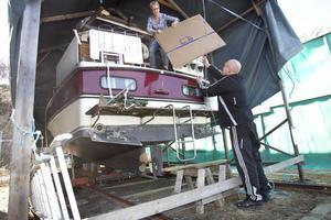 Lena Larsson langar en kartong till maken Lasse. Snart flyttar de och båten ska säljas.
