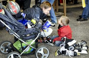 Lastvagn. Yngste sonen har rymt från sin barnvagn, medan den äldste, Joel, tålmodigt provar skridskor tillsammans med mamma Maria Malmberg.