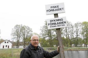 Håkan Berglin visar skylten som finns vid badplatsen. Men han och andra efterlyser också en skylt med bild som visar också den som inte kan svenska att man det är farligt att dyka vid badplatsen.