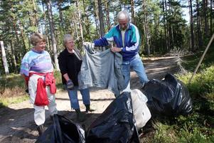 Bengt Lindgren visar upp en gammal kavaj som bärplockarna lämnat efter sig. Bredvid honom hustrun Ulla-Britt Lindgren och Birgitta Eriksson, som äger en del av marken.