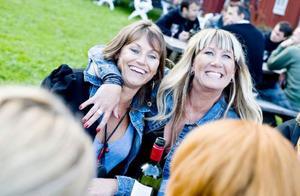 Åsa Sahlin (till höger) tar ett stadigt tag om väninnan Monika Schleenvoigt och gungar med i allsången.
