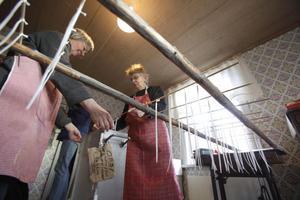 Eva Åström och Ann-Marie Bergman stöper ljus i långa banor till försäljning.