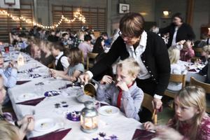 Läraren Elvy Fridner serverar äppeldryck åt Ludvig Andersson.
