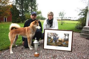 Segrare. Hunden Nadia har fått syn på något i gruset. Hussarna Daniel Larsson och Linda Haga poserar med de vunna priserna från älghunds-SM.