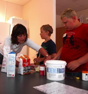 Grahamsbullar. Jakob Magnus och Rikard Daniels får hjälp av Solveig att mäta upp rätt mängd ingredienser till degen.