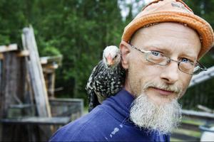 Peter Blombergsson poserar med en kärvänlig höna.   Det är bara en av flera djur som huserar på gården strax utanför Kall. Foto: Ulrika Andersson