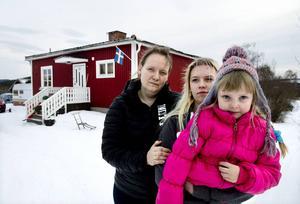 Hustrun Maria och döttrarna Nadja och Lisa framför huset. De är oroliga för hur framtiden ska se ut.