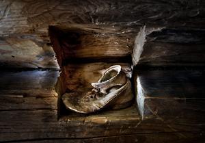I en stock i trappan mellan våningarna står en barnsko som hittades i huset under renoveringen-