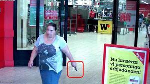 Här syns en av de åtalade kvinnorna på väg ut från en affär efter att ha försökt ta ut pengar.