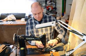 Skinnaren Täpp Lars i arbete vid den gamla pälssymaskinen.